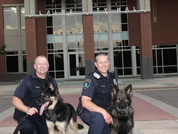 Officer Greg Rowe with Gunner and Officer Mark Allen with Remy in front of Blaine City Hall